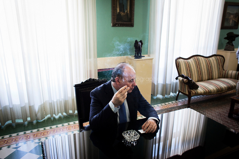 Reggio Calabria, Italy - 30 August, 2012: President of the Province of Reggio Calabria Giuseppe Raffa, 53, smokes a sigarette in his office in Reggio Calabria, Italy, on August 30, 2012.<br /> <br /> Calabria is one of the poorest Italian regions which suffers from lack of basic services (hospitals without proper equipment, irregular electricity and water), the product of disparate political interests vying for power. The region is dominated by the 'Ndrangheta (pronounced en-Drang-get-A), which authorities say is the most powerful in Italy because it is the welthiest and best organized.<br /> <br /> The region today has nearly 20 percent unemployment, 40 percent youth unemployment and among the lowest female unemployment and broadband Internet levels in Italy. Business suffer since poor infrastructure drives up transport costs.<br /> <br /> Last summer the European Union's anti-fraud office demanded that Italy redirect 380 million euros in structural funding away from the A3 Salerno - Reggio Calabria highway after finding widespread evidence of corruption in the bidding processes.