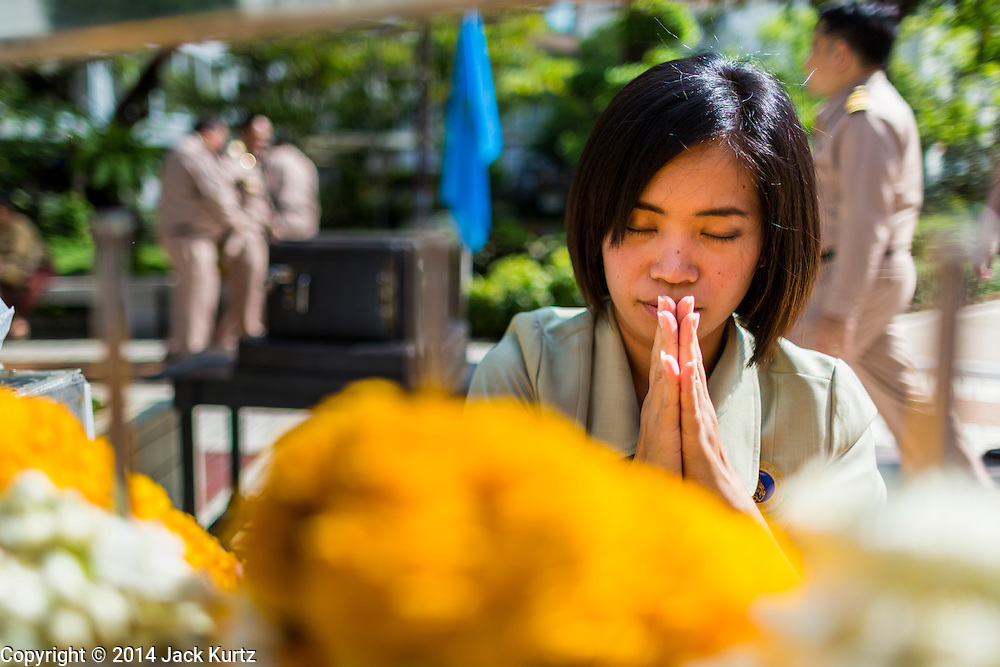 09 OCTOBER 2014 - BANGKOK, THAILAND:  A woman prays for Bhumibol Adulyadej, the King of Thailand in the plaza in front of Siriraj Hospital. The King has been hospitalized at Siriraj Hospital since Oct. 4 and underwent emergency gall bladder removal surgery Oct. 5. The King is also known as Rama IX, because he is the ninth monarch of the Chakri Dynasty. He has reigned since June 9, 1946 and is the world's longest-serving current head of state and the longest-reigning monarch in Thai history, serving for more than 68 years. He is revered by the Thai people and anytime he goes into the hospital thousands of people come to the hospital to sign get well cards.  PHOTO BY JACK KURTZ