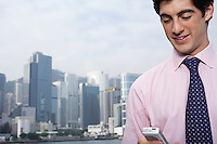 Young business man using mobile phone office buildings in background