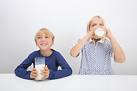 Little children drinking milk at table