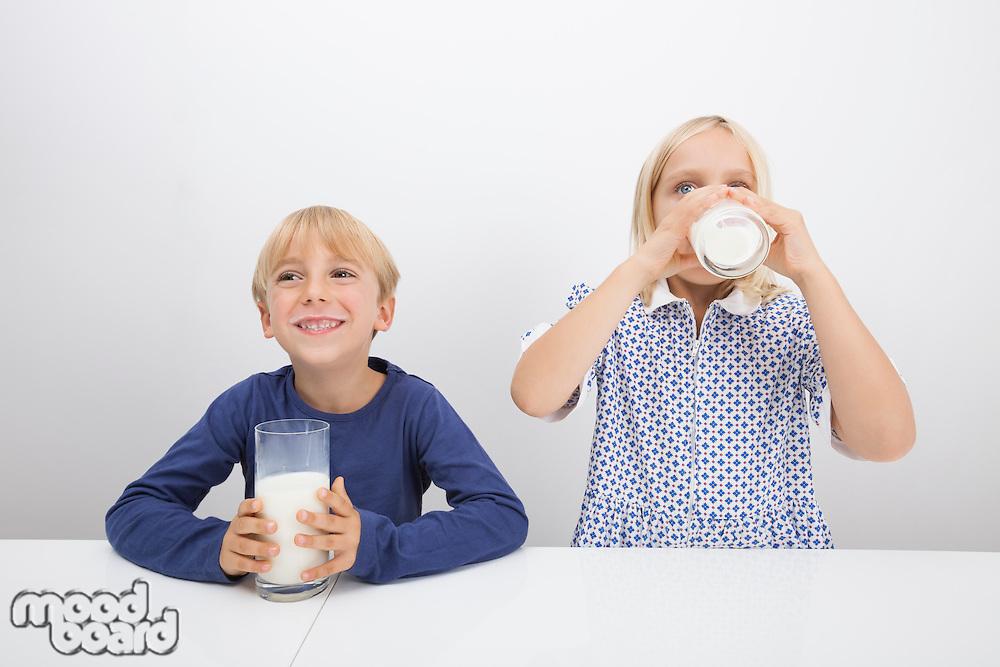 Little children drinking milk at table