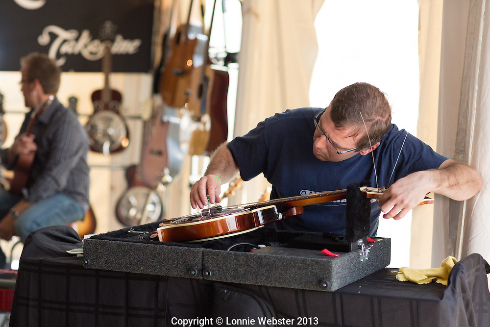 Bill Kasier Music Instructor installs new strings and tunes instruments for Fender customers during Merlefest 2013