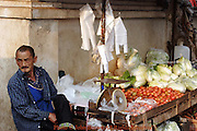 A sidewalk food vendor awaits early morning customers at a wooden lettuce and tomato stand in Mae Hong Son, Thailand.