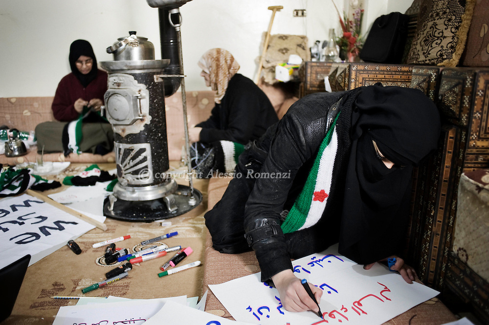 SYRIA - Al Qsair. In many houses, women of Al Qsair give their help for the revolution sewing scarves, hats and flags and writing banners for demonstration, with the colors of the old Syrian flag (the flag of the revolution) black, green and white with three red stars in the middle, on January 25,  2012. Al Qsair is a small town of 40000 inhabitants, located 25Km south-west of Homs. The town is besieged since the beginning of November and so far it counts 65 dead. ALESSIO ROMENZI