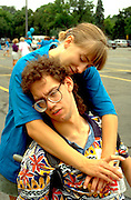 Counselor hugging man at Vinland Breaking Barriers disability demonstration age 24. St Thomas College St Paul  Minnesota USA