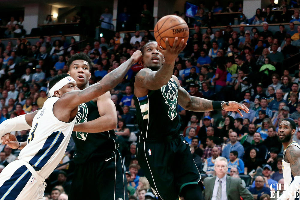 01 April 2018: Milwaukee Bucks guard Eric Bledsoe (6) goes for the layup past Denver Nuggets guard Torrey Craig (3) and Milwaukee Bucks forward Giannis Antetokounmpo (34) during the Denver Nuggets 128-125 victory over the Milwaukee Bucks, at the Pepsi Center, Denver, Colorado, USA.
