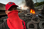 16 MAY 2010 - BANGKOK, THAILAND: An anti government Red Shirt at a burning tire barricade in Bangkok Sunday. Thai troops and anti government protesters clashed on Rama IV Road again Sunday afternoon in a series of running battles. Troops fired into the air and unidentified snipers shot at pedestrians on the sidewalks. At one point Sunday the government said it was going to impose a curfew only to rescind the announcement hours later. The situation in Bangkok continues to deteriorate as protests spread beyond the area of the Red Shirts stage at Ratchaprasong Intersection. Many protests now involve people who have not been active in the Red Shirt protests and live in the vicinity of Khlong Toei slum and Rama IV Road. Red Shirt leaders have called for a cease fire, but the government indicated that it is going to go ahead with operations to isolate the Red Shirt camp and clear the streets.      PHOTO BY JACK KURTZ