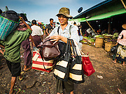 """25 OCTOBER 2015 - INSEIN, MYANMAR:  A man sells purses and bags at Danyin Market (also known as Da Nyin) in Insein, Myanmar, about 90 minutes from Yangon. Vendors in the market sell just about everything people in the area need, but mostly it's a """"wet market"""" with fruits, vegetables and meats. Most people in Myanmar still do not have refrigerators in their homes, so people go to market almost every day.    PHOTO BY JACK KURTZ"""