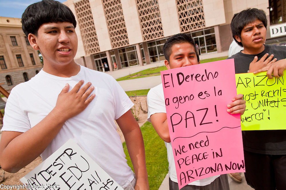 """14 MARCH 2011 - PHOENIX, AZ: Public school students say the """"Pledge of Allegiance"""" during an immigrants' rights protest at the Arizona State Capitol in Phoenix Monday. Protests by immigrants' rights activists have continued as the state's conservative Republican legislators debate toughening the state's anti-immigrant bills. Some of the bills the state legislature has debated this year include eliminating birthright citizenship, a law that would require hospitals to check the immigration status of patients checking in for elective care, a bill that would require schools to verify the immigration status of students when they enroll and a bill that would require law enforcement to impound the cars of undocumented immigrants even if they have a legal driver's license from another state.      Photo by Jack Kurtz"""