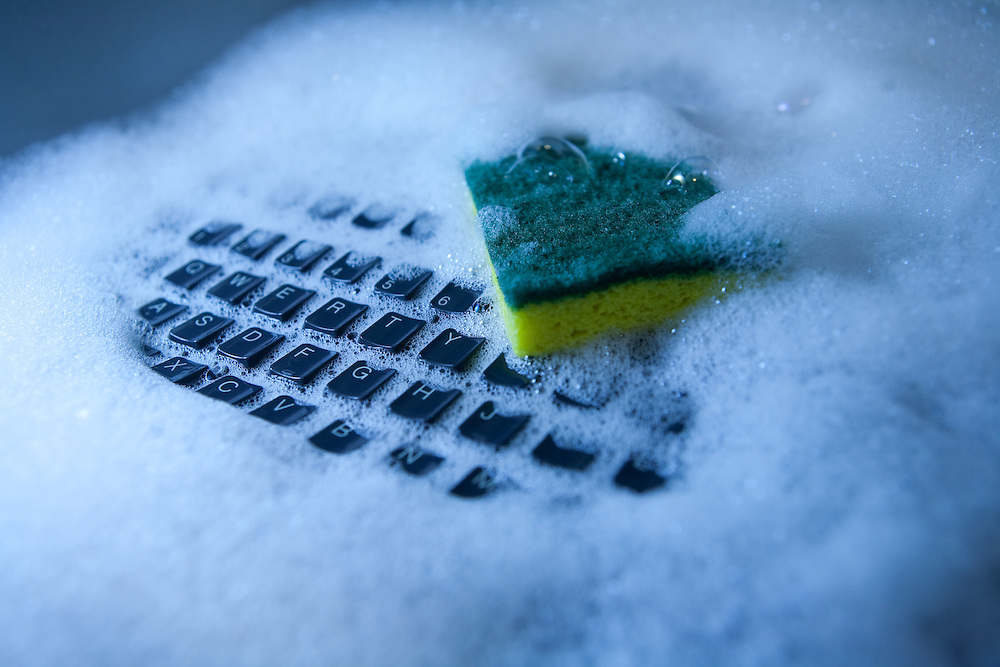 Computer keyboard in a sink full of soapy water with a yellow and green sponge.