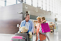 Family on holiday trip walking in airport with lens flare