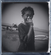 Young Filipino boy wades in shallow water close to shore with a big smile on his face, Palawan Island, Philippines, Southeast Asia