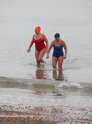 © Licensed to London News Pictures. 26/12/2014. Southsea, Hampshire, UK. Two women coming out of the water having taken a dip in the calm sea today, Boxing Day, in Southsea, Hampshire. Photo credit : Rob Arnold/LNP