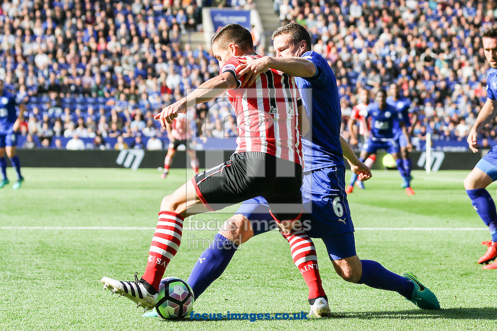 Robert Huth of Leicester City (right) tackles Dusan Tadic of Southampton (left) during the Premier League match at the King Power Stadium, Leicester<br /> Picture by Andy Kearns/Focus Images Ltd 0781 864 4264<br /> 02/10/2016
