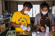 03 MARCH 2104 - MAE KASA, TAK, THAILAND:  Workers in the pharmacy count out patients' medications at the Sanatorium Center for Border Communities in Mae Kasa, about 30 minutes north of Mae Sot, Thailand. The Sanatorium provides treatment and housing for people with tuberculosis in an isolated setting for about 68 patients, all Burmese. The clinic is operated by the Shoklo Malaria Research Unit and works with several other NGOs that assist Burmese people in Thailand. Reforms in Myanmar have alllowed NGOs to operate in Myanmar, as a result many NGOs are shifting resources to operations in Myanmar, leaving Burmese migrants and refugees in Thailand vulnerable. Funding cuts could jeopardize programs at the clinic. TB is a serious health challenge in Burma, which has one of the highest rates of TB in the world. The TB rate in Thailand is ¼ to ⅕ the rate in Burma.        PHOTO BY JACK KURTZ