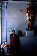 Woman standing beside statue of crucified Christ at a Catholic Church on the island of Kayts. Jaffna Peninsula.<br /> St. Mary's Church. 2002