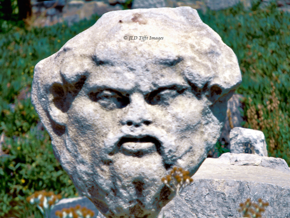 Architectural fragment of a mask on the ground at Bodrum Castle, Turkey.  The expression is severe.  Moustache and beard, protruding ears.
