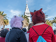 """Two women wear """"pussy hats"""" of fur while standing in Justin Herman Plaza for the International Women's Day rally before the march."""