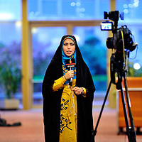 Iran state TV anchor woman wearing Islamic dress addressing a camera at the press center during  the first round of the E3/EU+3 Iran talks in Geneva concerning Iran's nuclear program. E3/EU +3 refers to UK, France and Germany plus U.S., Russia and China.