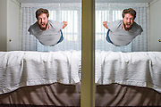 Fort Wayne, Indiana - August 15, 2014: Jumping on the bed at the Residence Inn, Marriot in Fort Wayne, Indiana. I'm reflected in a mirror. This hotel room was huge! <br />