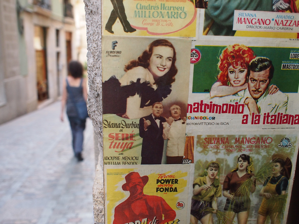 A woman walks down a street in Girona, Spain, with Italian movie posters in the foreground.