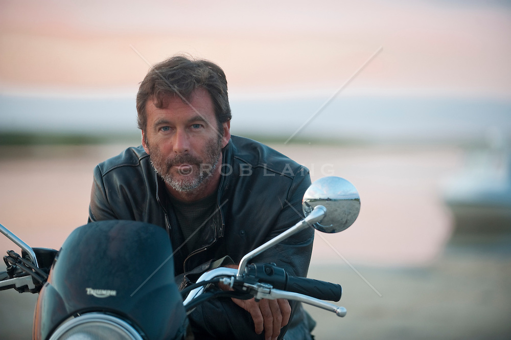 Man in a leather jacket sitting on his mototcycle looking at camera