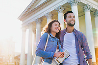 Portrait of young attractive couple standing against museum with lens flare in background