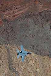 "A US Navy Boeing F/A-18F Super Hornet from Strike Fighter Squadron 122 (VFA-122) the ""Flying Eagles"" flies through the Jedi Transition over Rainbow Valley, Death Valley National Park, California, United States of America"