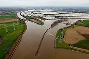 Nederland, Limburg, Gemeente Maasgouw, 15-11-2010; Hoogwater in de Maas met midden links de sluis van Osen (sluiscomplex Heel) die direct toegang geeft tot de Maas naar Roermond via de dubbelsluis van het Lateraalkanaal. De kleinere sluis (r) geeft toegang tot de Maas naar Roermond. Voor schepen naar het noorden biedt het kanaal een kortere en snellere route dan de oorspronkelijke Maasroute. De aanleg van het sluiscomplex zorgde er voor dat een enorme bocht in de Maas afgesneden kon worden (de Lus van Linne). Midden rechts Stuw van Linne, met waterkrachtcentrale naast de stuw. Links van de stuw de Overlaat van Linne (l) met een oude Maasarm. .Rising water at river Meuse, with lock complex at Heel with double-lock for the Lateral canal (l). For ships to the north, the channel offers a shorter and faster route than the original Maasroute. The construction of the lock complex cut of a huge bend in the Meuse(the Loop of Linne). .At the middle Linne Spillway with hydroelectric plant (r) and Linne Spillway with an old branch of river Meuse. .luchtfoto (toeslag), aerial photo (additional fee required).foto/photo Siebe Swart