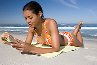 Young woman in retro swimwear lies on beach reading a book