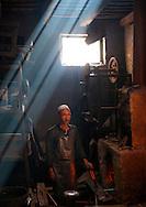 Blacksmith in his workshop, Xinjiang Uyghur autonomous region, China.