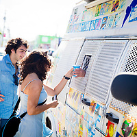 MIAMI, FLORIDA -- July 11, 2015 -- People enjoy Wynwood Walls featuring the work of several artists during the colorful and vibrant Art Walk in the Wynwood Art District Miami, Florida.  The event on the second Saturday of every month features not only public art, but gallery tours, dining at a myriad of restaurant and a party atmosphere after dark.  (PHOTO / CHIP LITHERLAND)