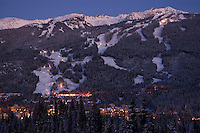 Blackcomb Mountain in the purple twilight of an early winter evening rises above Whistler Village, BC Canada.