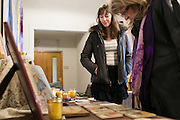Rachel Dow of Rochester, left, shares her work with visitors at Elton Street Artisan Market in Rochester on Sunday, December 20, 2015. Some of Rachel's work uses scraps from Dave's woodworking.