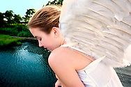 Girl in Angel costume looking down on Marsh Bay in early dusk. Taken at Levy Park, Merrick, Long Island, NY, USA.