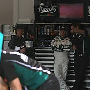 Sprint Cup Series driver Dale Earnhardt Jr. talks with crew members  in the garage at the Daytona International Speedway on February 18, 2011 in Daytona Beach, Florida. (AP Photo/Alex Menendez)