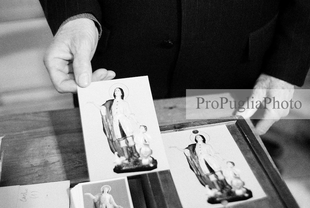 Reportage sviluppato ad Alessano (LE). Viene presa in considerazione fotograficamente, la gente che popola il paese nei suoi bar, piazze, strade, giardini pubblici. Ed, insieme a questa, i particolari e gli eventi caratterizzanti il luogo...Domenica delle Palme..Uomo mostra icone sacre durante la santa messa.