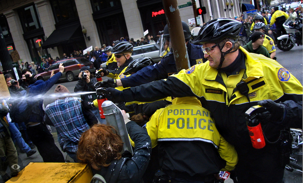 March 25, 2003 -Portland Police officers spray protesters who were crowded on the sidewalk at the intersection of Washington and 3rd. The group was shouting out for the police not to arrest another protester when the officers let loose.