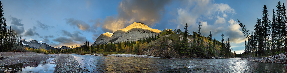 Sunrise spotlights Mount Kidd and reflects in Kananaskis River in the Kananaskis Range of the Canadian Rockies, Alberta, Canada. Access the Mt Kidd Interpretive Trail from the huge Mt Kidd RV Park. Kananaskis Country is a park system west of Calgary. This panorama was stitched from 4 overlapping photos.