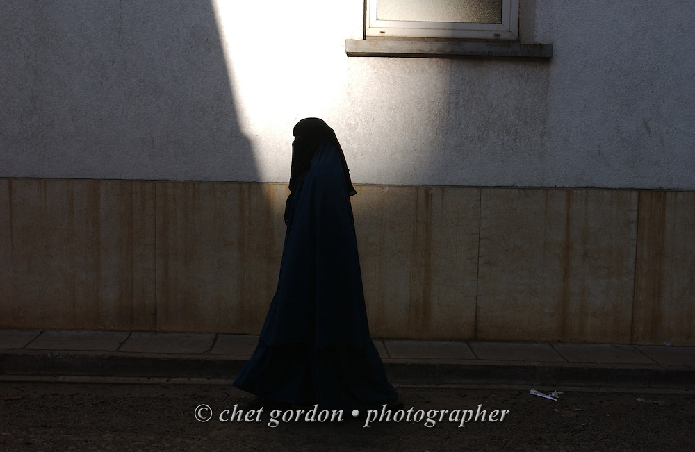 A Muslim woman walks in an alleyway adjacent to a mosque in downtown Nairobi, Kenya on Monday, January 26, 2004.
