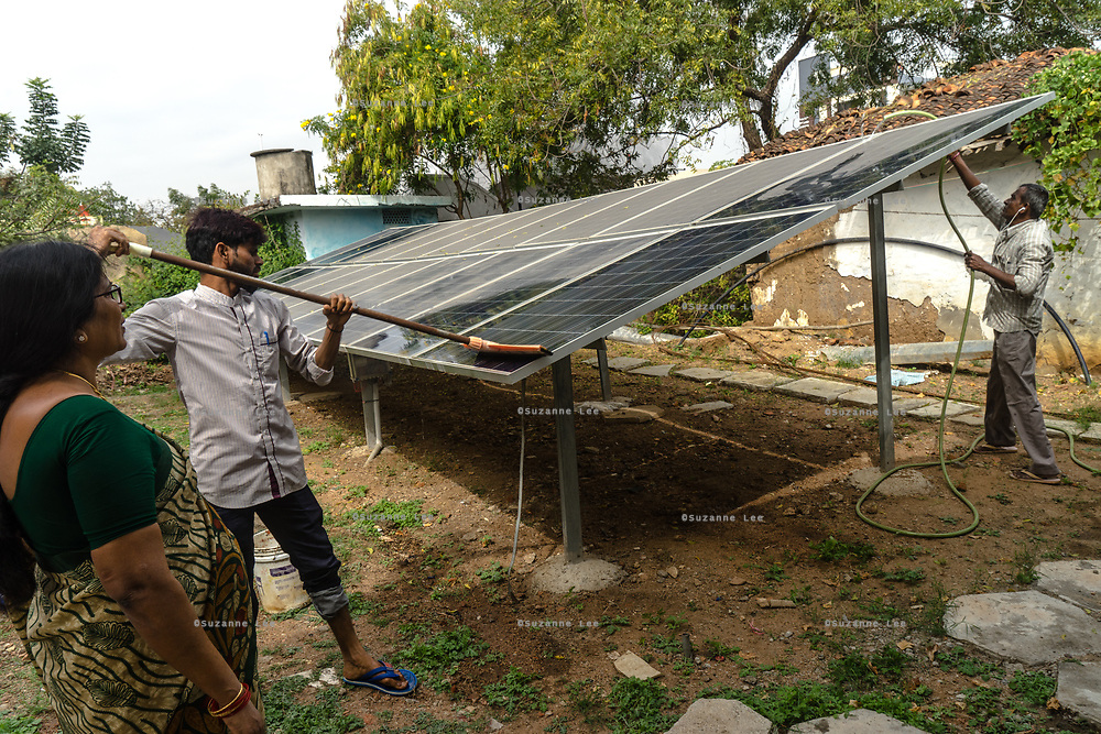 Padmaja, Safe Water Network iJal station operator, left, stands as her employees clean solar panels at the facility in Rangsaipet, in Waragal, Telangana, Indiia, on Saturday, February 9, 2019. Photographer: Suzanne Lee for Safe Water Network