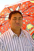 Handsome Hmong man enjoying festivities under colorful sun umbrella. Hmong Sports Festival McMurray Field St Paul Minnesota USA