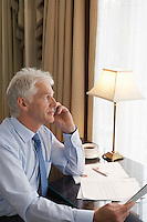 Business man using mobile phone sitting at desk elevated view