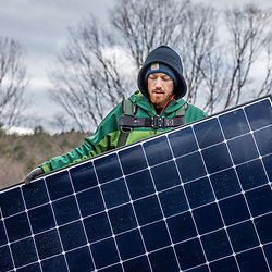 A PV Squared employee installing solar panels on the roof of a barn in Shelburne, Massachusetts.