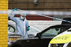 © Licensed to London News Pictures. 08/08/2017. LONDON, UK. A forensic officer takes samples from a car at the crime scene cordon on the corner of Old Kent Road and Ilderton Road, next to the Afrikiko Bar Restaurant and Club. Police were called at around 2am and found a 19 year old man with stab injuries, who was pronounced dead about an hour later. Five people have now been arrested in connection with stabbing and are being held at a south London police station.  Photo credit: Vickie Flores/LNP