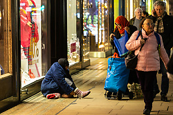 A woman in a headscarf stops to offer food and wooden slippers to a barefoot beggar on Oxford Street. Homeless Britons are coming under increasing pressure as a surge of Roma beggars from Romania arrive on the streets of London to take advantage of the generosity of Christmas shoppers. London, December 04 2018.