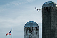 Montgomery, New York - A DJI Inspire 1 quadcopter flies in front of silos and the American flag at Benedict Farm on Jan. 25, 2015.
