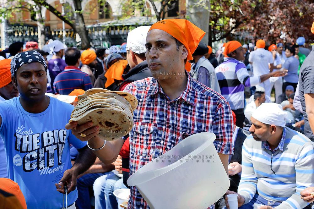 Roma  14 Aprile 2013.Processione religiosa, a Piazza Vittorio, per celebrare Vaisakhi il nuovo anno per i Sikh, che coincide tradizionalmente nel Punjab con il primo raccolto delle colture dell'anno. Un sikh offre il  chapati, il pane indiano.
