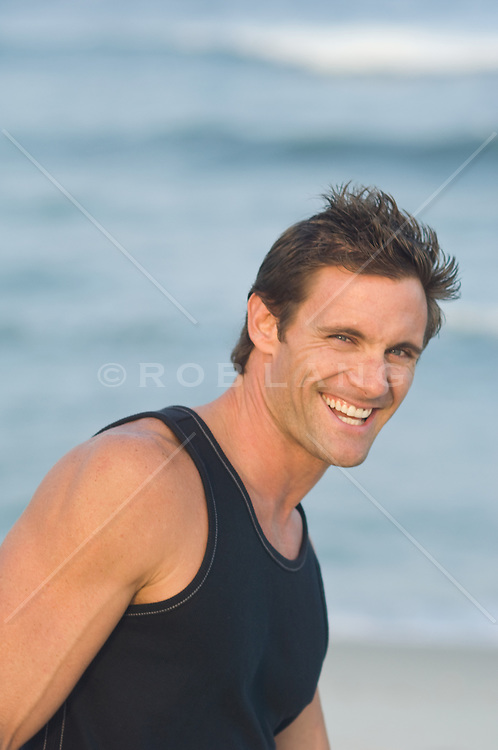 Man in a black tank top with a big smile