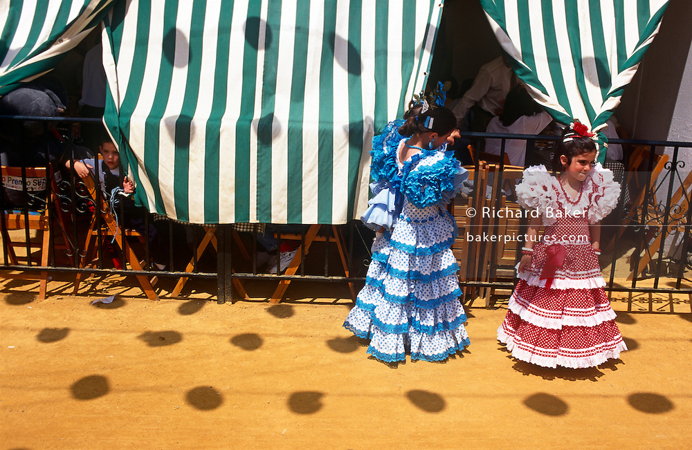 Two young spanish girls play outside a family Caseta during the Spring Feria in Seville, Spain. Both dressed in traditional flamenco dresses, the two friends stand in bright sunshine as a younger boy peers out from the canopy screen that keeps the marquee interior cool. .It is a lively event that Seville holds annually in the vast fairground area on the far bank of the Guadalquivir River. Rows of temporary marquee tents, or casetas, host families, corporations and friends into the late hours during the April Fair which begins begins two weeks after the Semana Santa, or Easter Holy Week in the Andalusian capital.